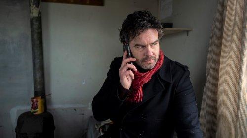 Een man met donkere krullen en een grijs baardje zit met een jas aan in een smoezelig huis. Hij drukt z'n mobiel tegen z'n oor en kijkt naar buiten.
