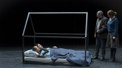 Vier mensen spelen toneel. Op een podium kijken een man en vrouw naar een stel dat in een bed ligt.