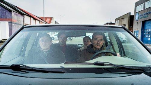 Vier volwassenen zitten in een auto. Ze kijken grimmig voor zich uit.