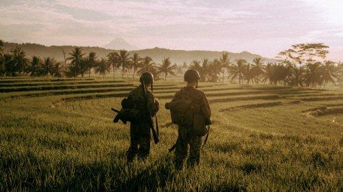 Twee soldaten kijken uit over een mooi, Indonesisch landschap.