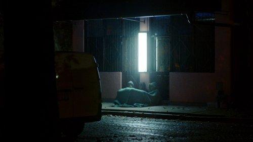 Drie jongens zitten in het donkre onder een deken op een stoep, met hun rug tegen een gebouw.