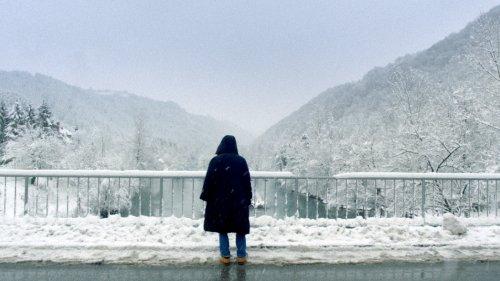 Een jongen in een jas met capuchon staat op een besneeuwde brug en kijkt uit over een riviertje tussen de bergen.