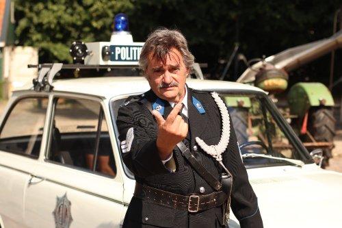 Een grijsharige politieagent wijst dreigend met zijn vinger.