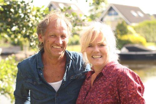 Een man en een vrouw staan naast elkaar in een waterrijke woonwijk en lachen breeduit.