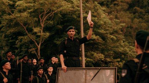 Een legerkapitein staat in een truck en houdt een envelop omhoog. Soldaten kijken naar hem op.