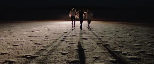 Drie mannen lopen naast elkaar in het donker over een zoutvlakte. De man rechts gebruikt een taststok.