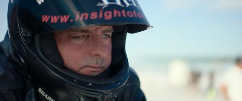 Ben, een man van middelbare leeftijd met een visuele beperking, draagt een zwarte motorhelm.
