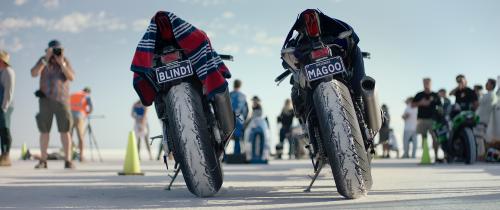 Twee motoren staan naast elkaar op een zoutvlakte met toeschouwers. Op het nummerbord van de linker motor staat BLIND1.