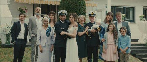 Een familie poseert met een bruidspaar. De bruidegom en een andere man dragen een uniform van de marine.