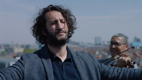 Een man met donkere krullen en een baardje staat met zijn ogen dicht en armen gespreid buiten. Hij wordt meegevoerd op de muziek van de violist die achter hem staat.