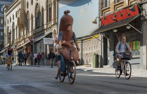 Een man in een worstenpak fietst door een winkelstraat. Achterop zit een meisje, dat hem vasthoudt om zijn middel.