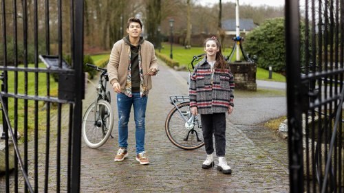 Een jongen en een meisje staan opgetogen voor een hek op een oprijlaan.
