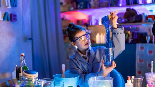 Een meisje met een veiligheidsbril op staat in een lab en kijkt naar blauw slijm.