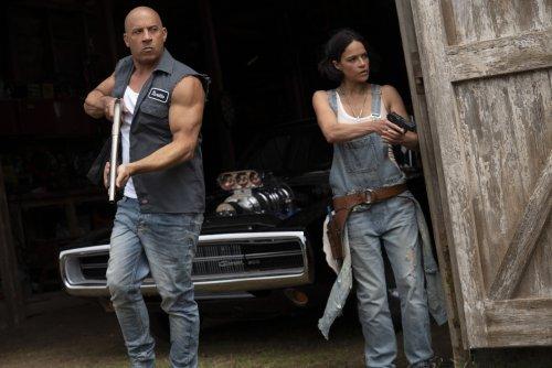 Een man en een vrouw kijken gewapend om de hoek van een schuur.