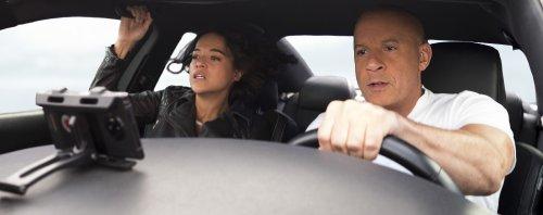 Een man en een vrouw zitten met gespannen gezichten in een auto. De vrouw op de passagiersstoel houdt zich stevig vast.
