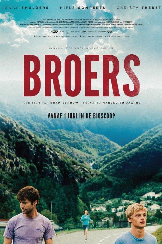 Broers. 2 jongens in t-shirt staan op een bergpas met achter hun groen begroeide bergen en in het dal een klein dorpje. Achter hun komt een meisje aangerend.