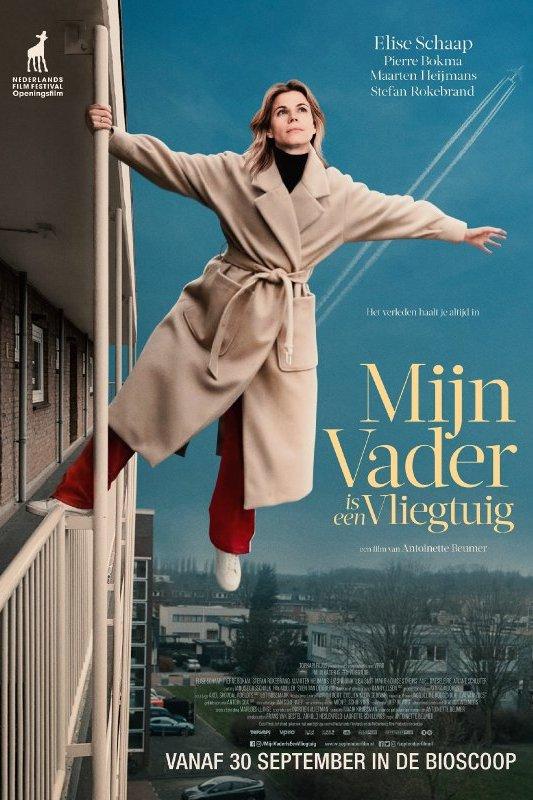 Mijn vader is een vliegtuig. Een vrouw in een beige trenchcoat houdt zich met een arm en één voet vast aan het balkon van een gebouw. Ze heeft haar armen gespreid en kijkt omhoog.