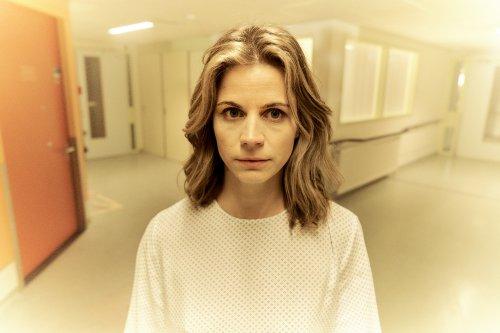 Een jonge vrouw in witte kleding staat in een lichte hal en kijkt verdwaasd voor zich uit.
